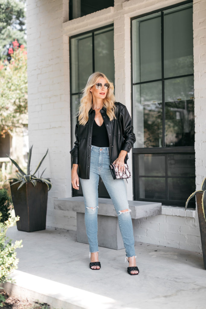 Dallas blogger wearing a black leather shirt jacket and faded blue jeans