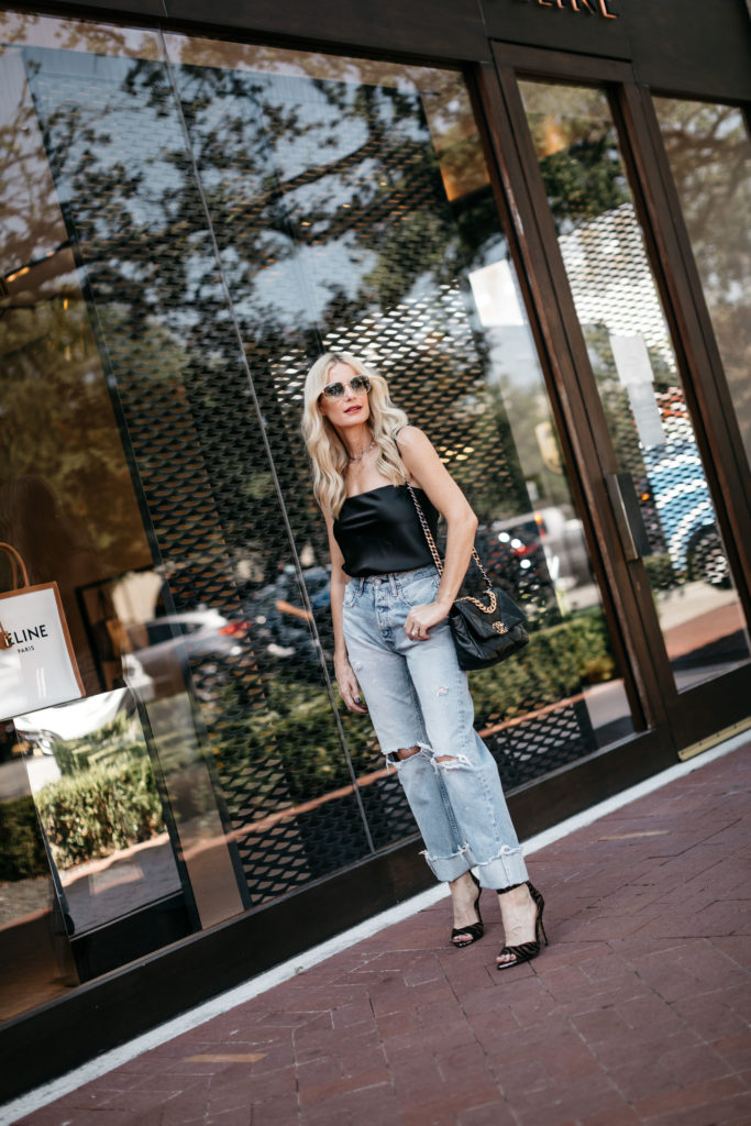 Fashion blogger wearing a strapless black top and cropped denim for fall