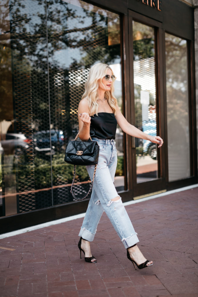 Dallas style blogger wearing ripped denim and a black date night top