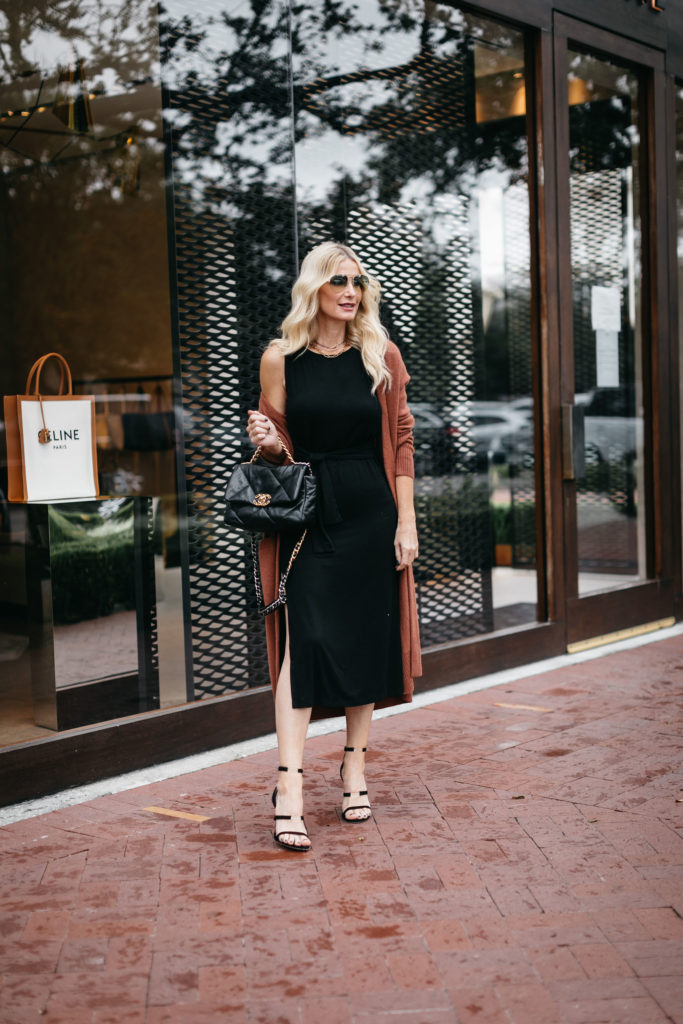 Dallas blogger wearing a rust cardigan and a black dress