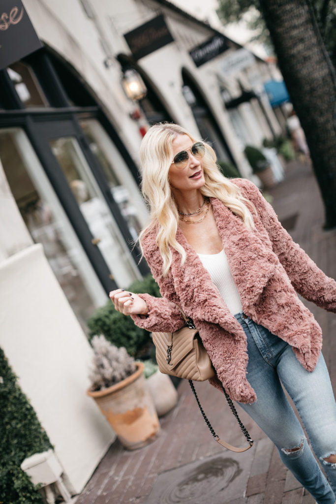 Fashion blogger wearing a pink fur jacket for fall and a white bodysuit