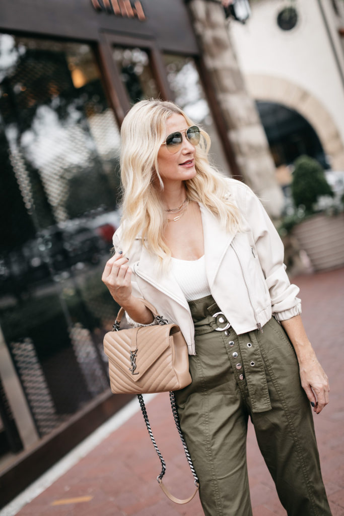 Fashion blogger wearing a neutral YSL bag and a faux leather white jacket