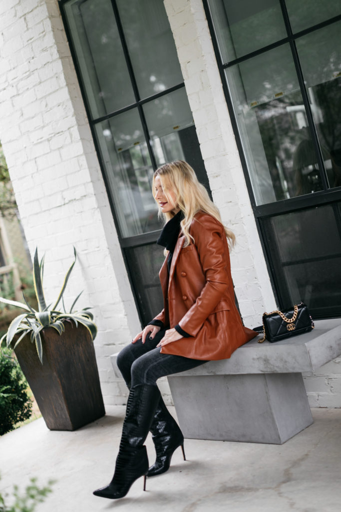 Dallas blogger wearing a rust faux leather jacket and knee-high black boots by Schutz