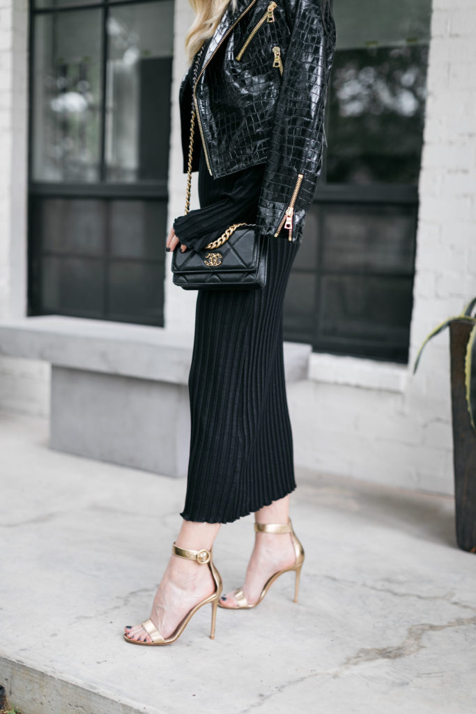 Dallas blogger wearing a black Moto jacket and a black dress with gold heels for fall