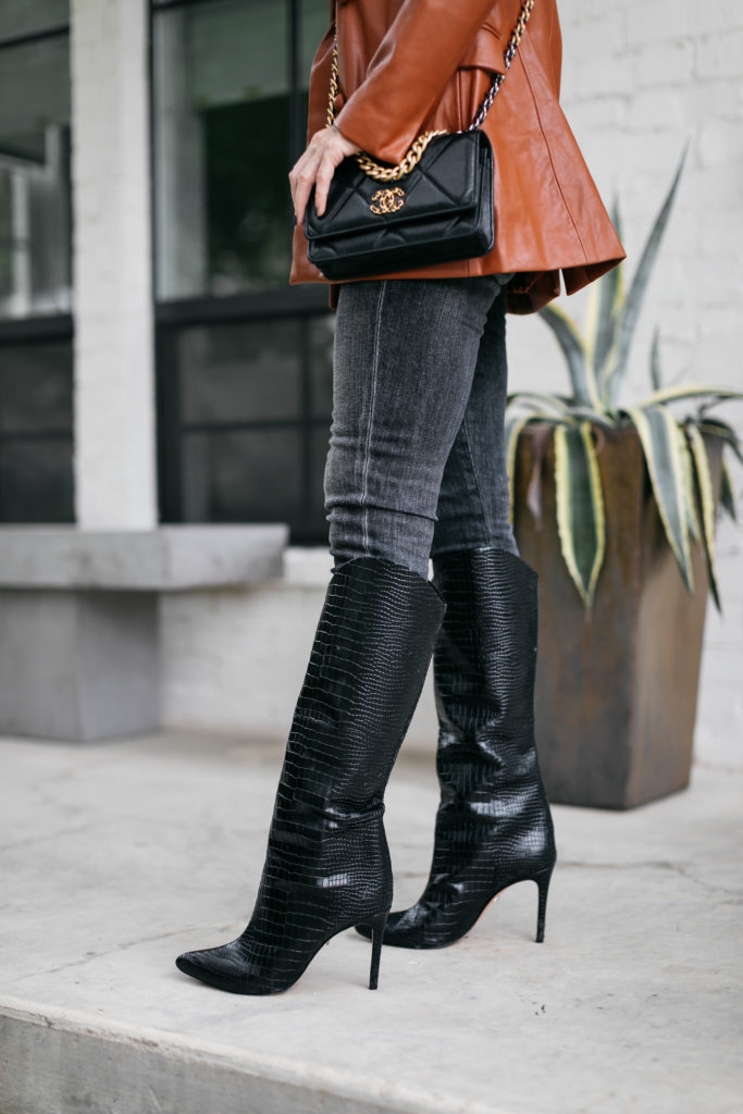 Fashion blogger wearing black knee-high boots and a Chanel handbag