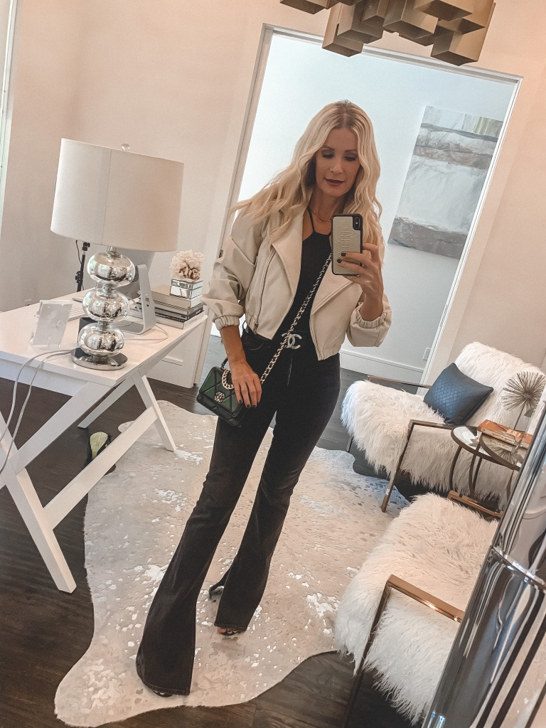 Dallas blogger wearing a cream leather jacket and black flare pants