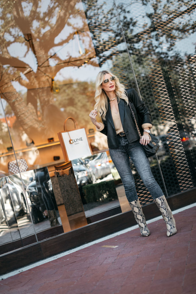 Dallas blogger wearing a black blazer and faded black denim with snake print boots
