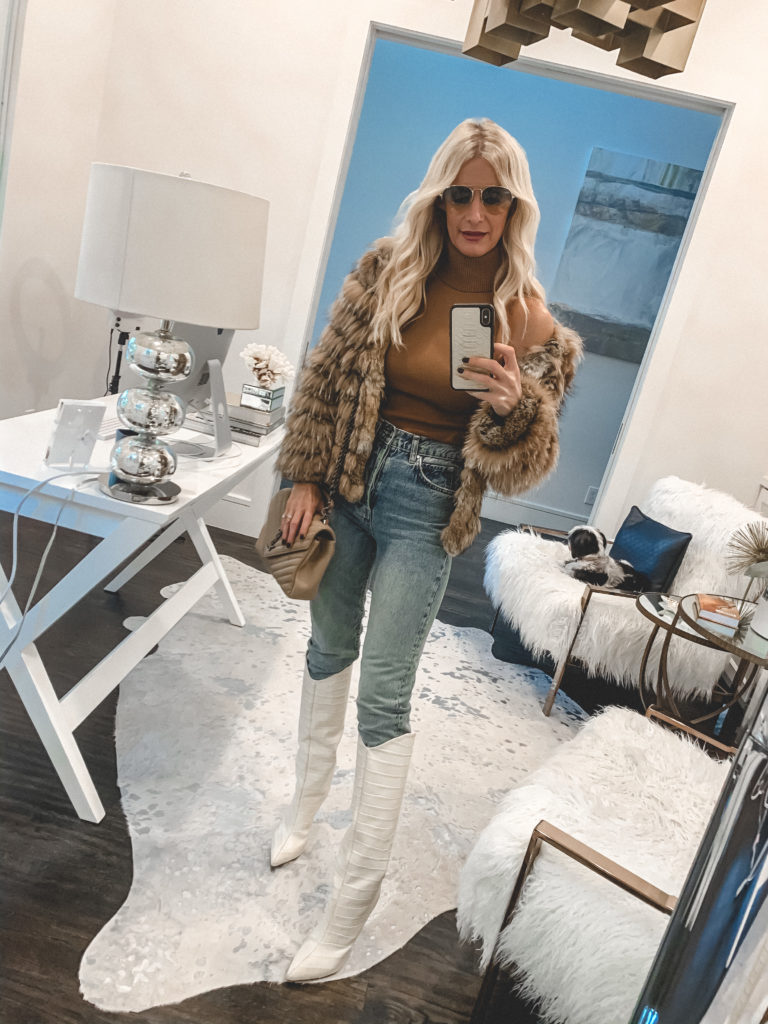 Dallas fashion blogger wearing a faux fur jacket and white knee high boots