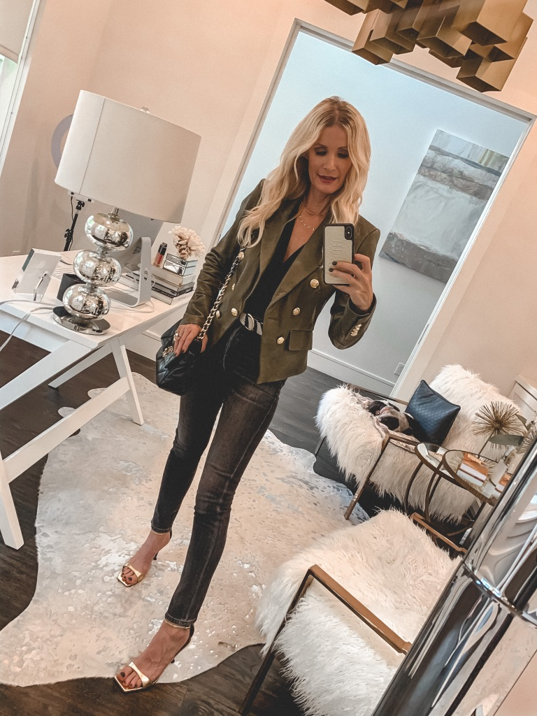 Dallas blogger wearing black denim and an army green jacket with gold hardware