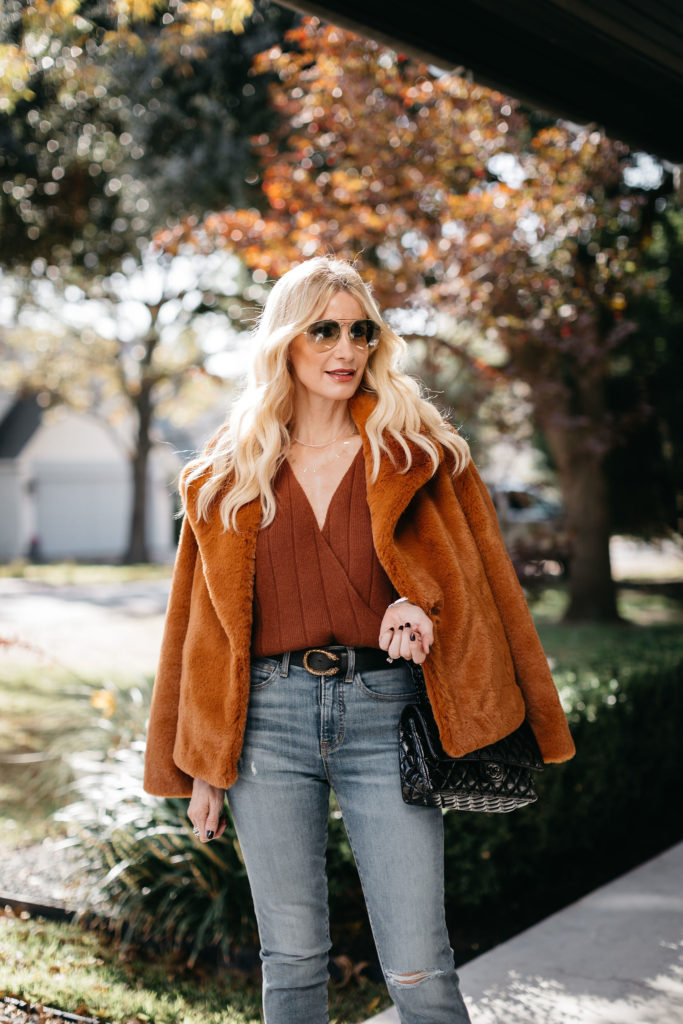Style blogger wearing a rust v-neck sweater and a black belt for winter