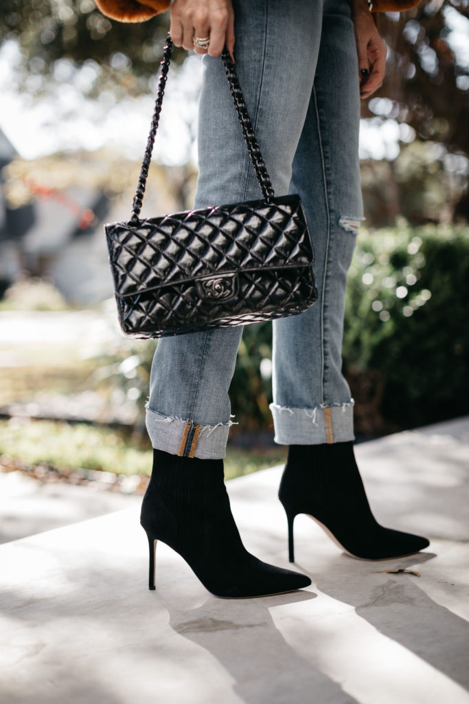 Dallas blogger wearing a black Chanel handbag and black heel booties