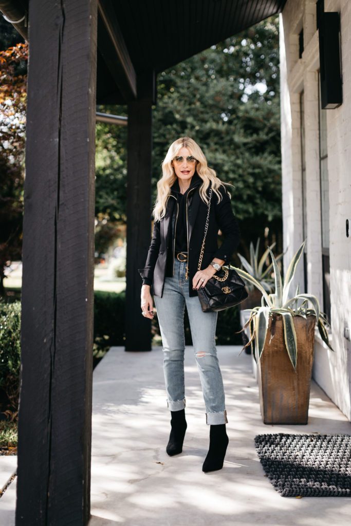 Fashion blogger wearing a black blazer and black booties in the winter