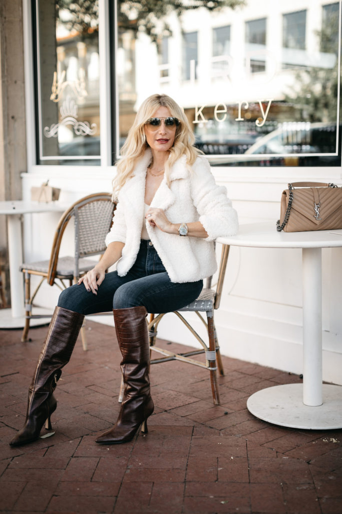Dallas fashion blogger wearing a white jacket and brown knee high boots