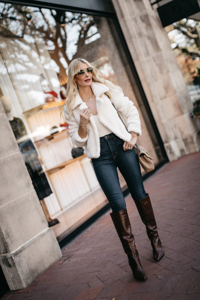 Dallas style blogger wearing a soft white jacket and denim with knee high boots