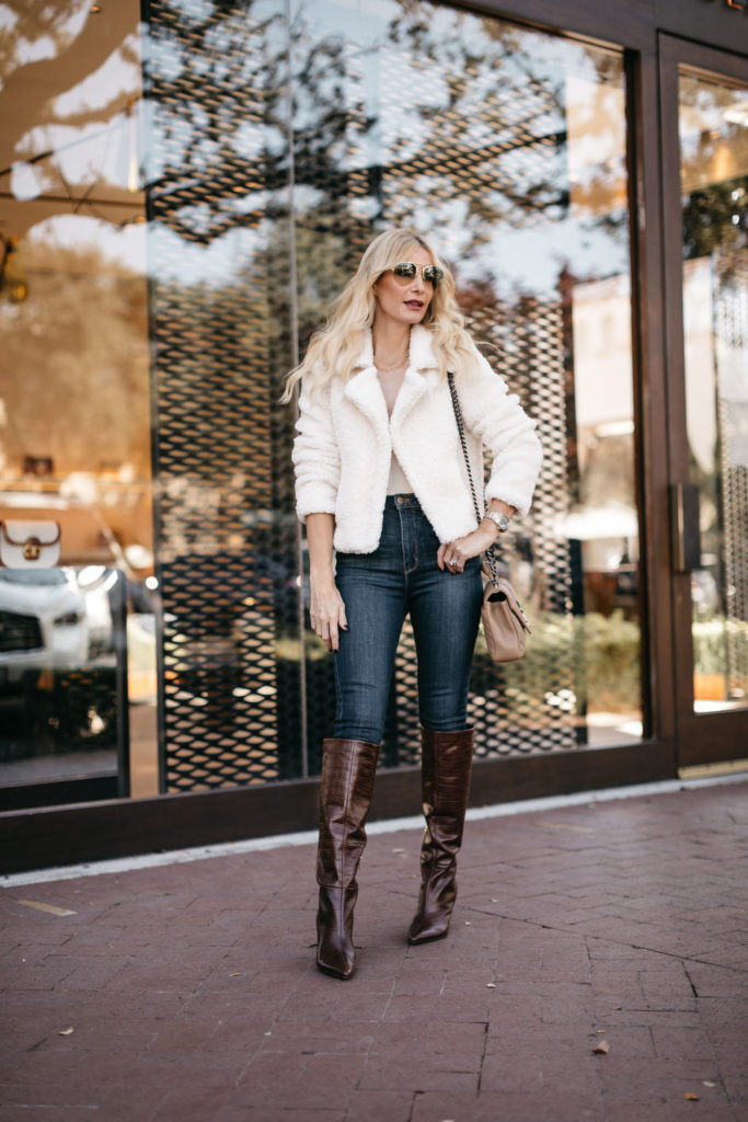 Dallas style influencer wearing brown snake print knee high boots and a white outfit
