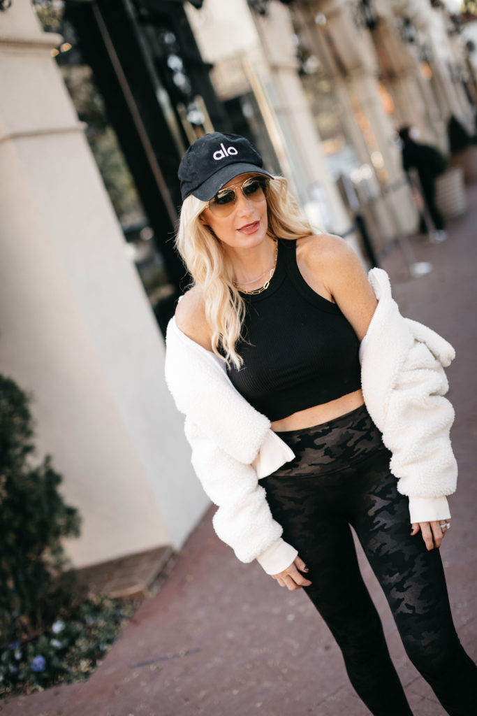 Dallas fashion blogger wearing a black workout bra and an Alo fitness hat
