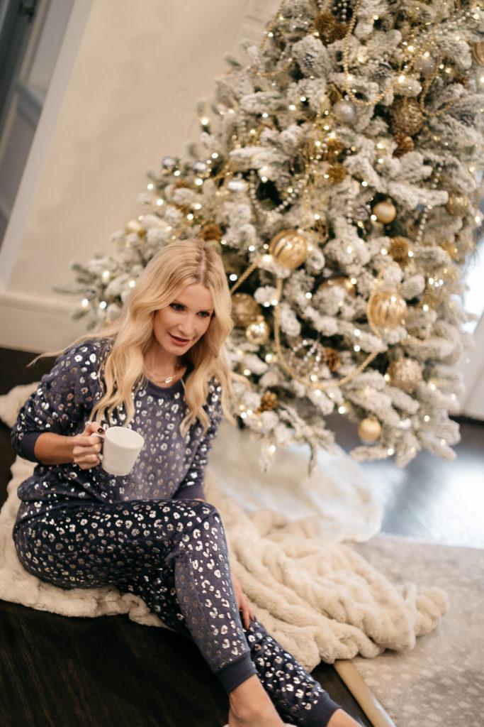 Dallas fashion blogger wearing a cozy PJ set by a Christmas tree