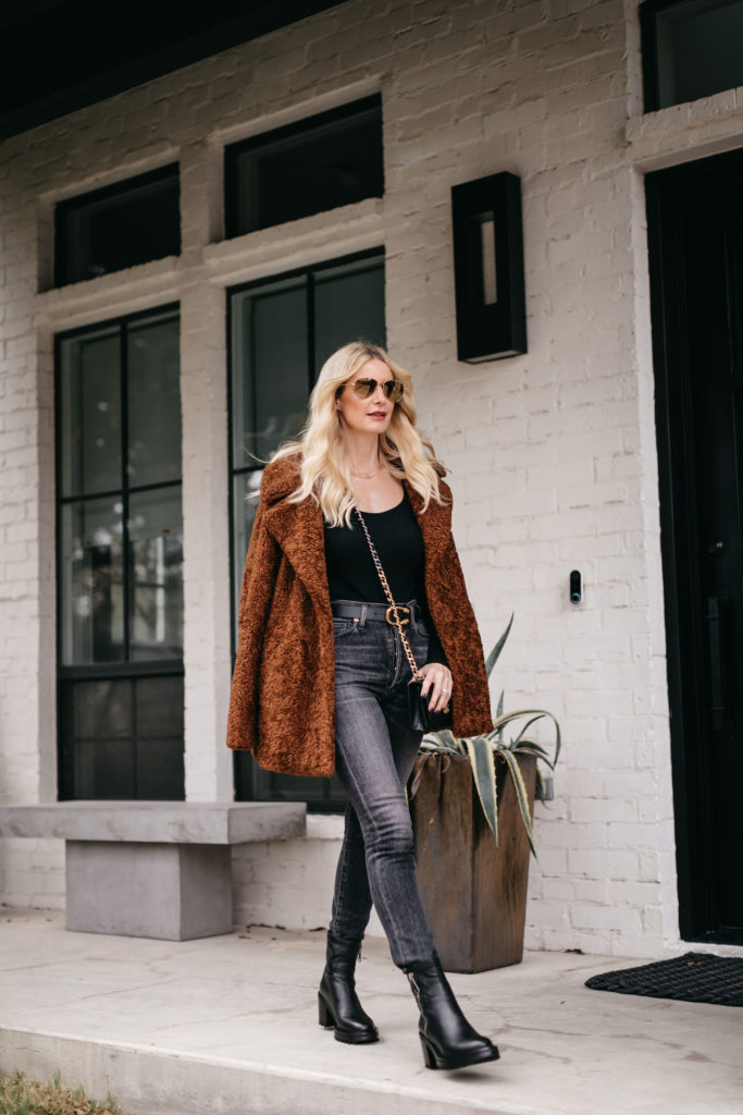 Fashion blogger wearing a faux fur jacket and black faded denim