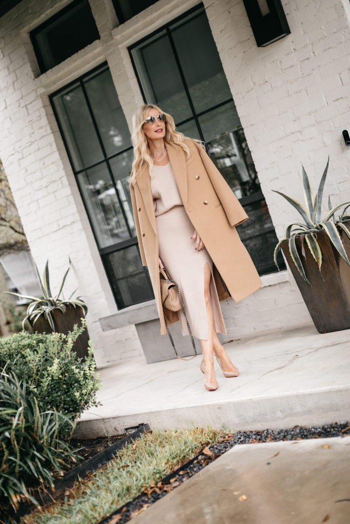 Style blogger wearing a camel coat and neutral skirt and heels for winter