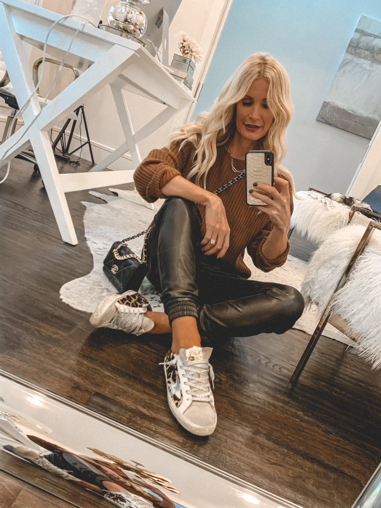 Dallas style blogger wearing a cozy chic camel sweater and faux leather joggers with sneakers