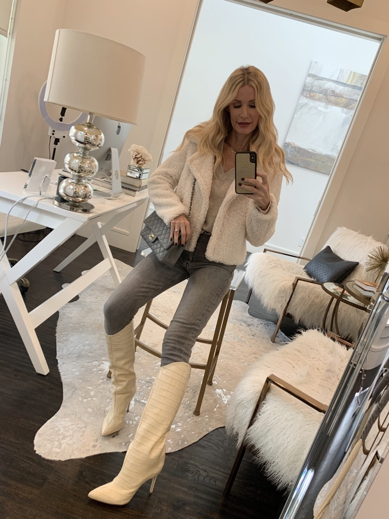 Dallas blogger wearing a winter white outfit with a faux fur jacket and white tall boots