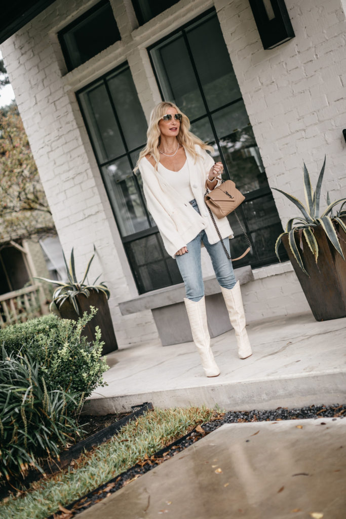 Dallas blogger wearing a cozy white cardigan and white knee high boots