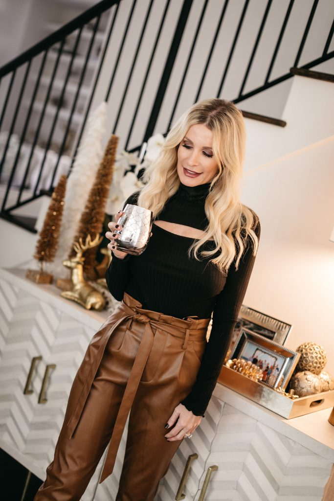 Style blogger wearing a ribbed black top for winter with faux leather pants