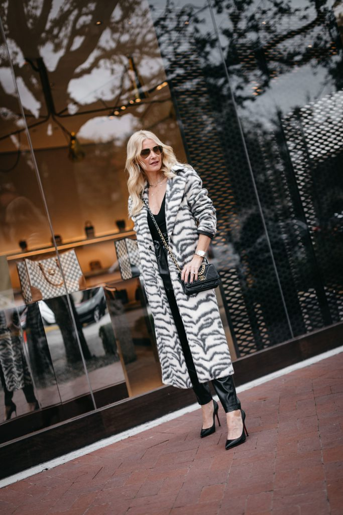 Style blogger wearing black faux leather pants and black heels