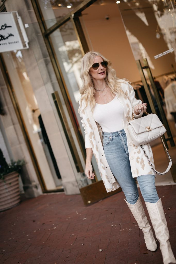Dallas blogger wearing a neutral leopard cardigan and light wash denim with white boots