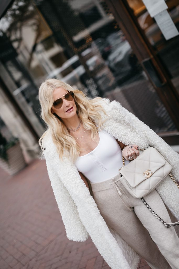 Dallas style blogger wearing a white teddy coat and a Chanel handbag with joggers