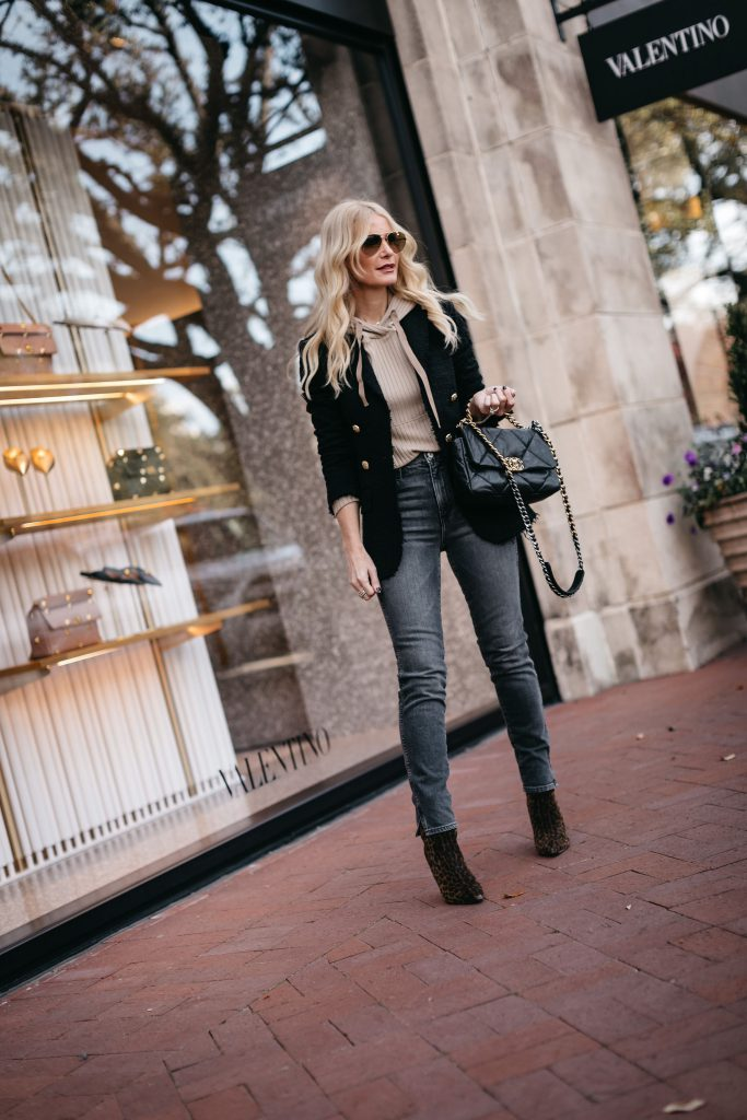 Fashion blogger wearing a blazer and a hoodie together and booties