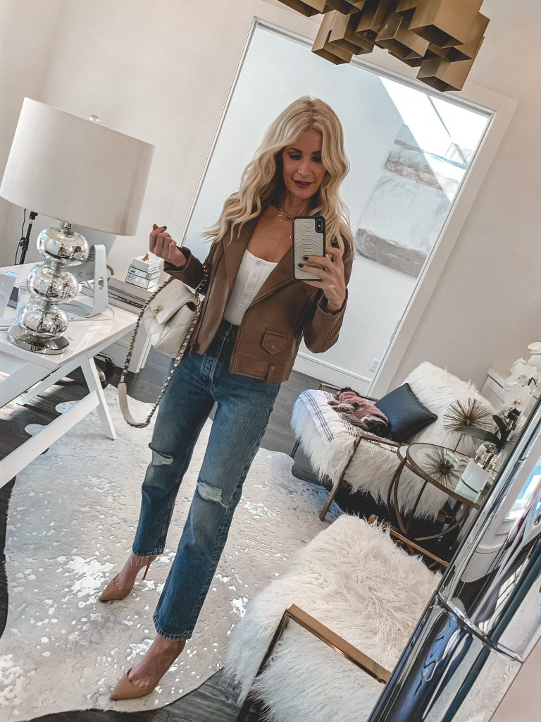 Fashion blogger wearing straight leg denim and a faux leather brown jacket