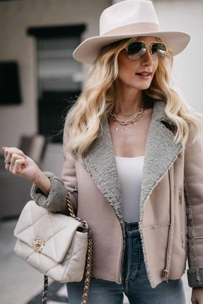 Dallas style blogger wearing a chic jacket and a white Chanel bag with a white hat for spring
