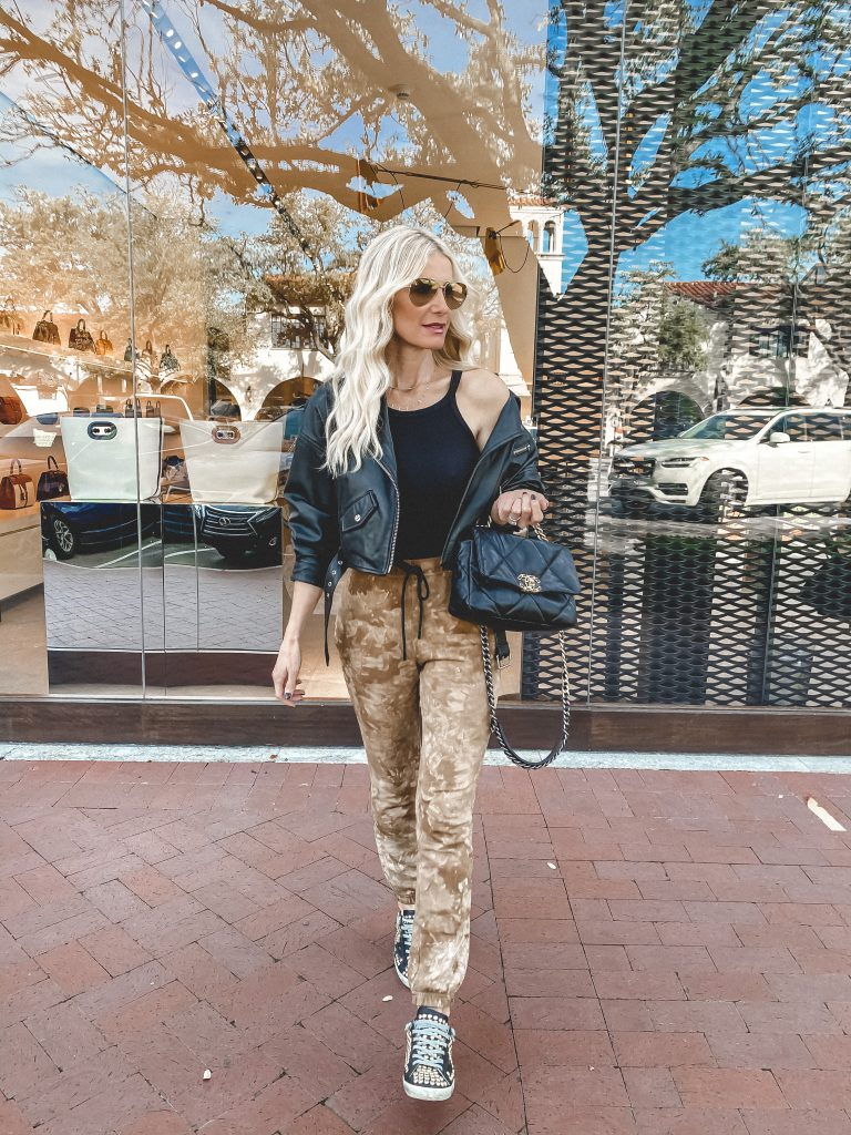 Dallas blogger wearing neutral tie dye joggers and a black Moto jacket