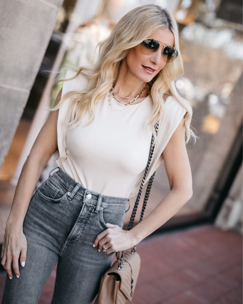Fashion blogger wearing a beige bodysuit and gold chain necklaces