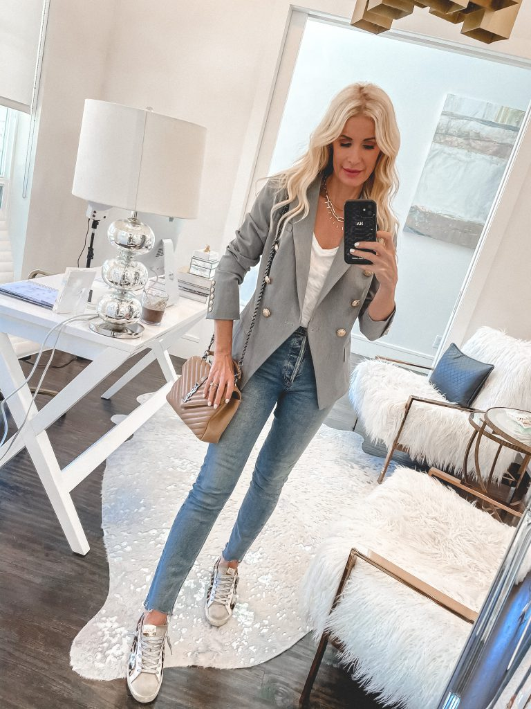 Dallas style blogger wearing a grey blazer with gold buttons and light wash denim