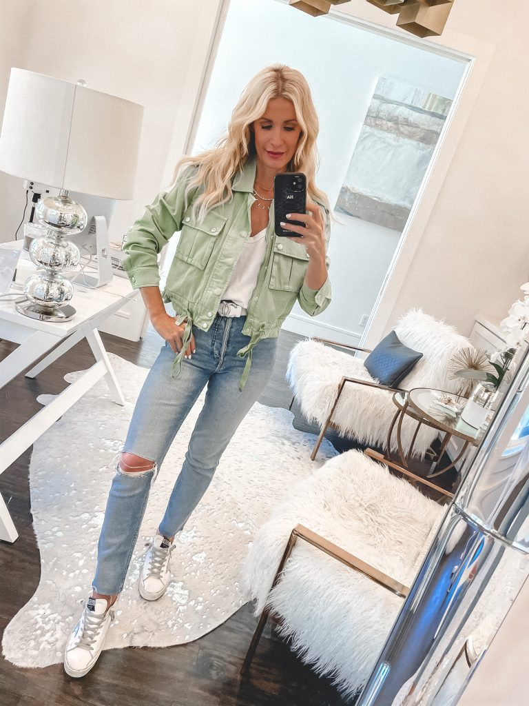 Fashion and style blogger wearing a green jacket with light wash denim