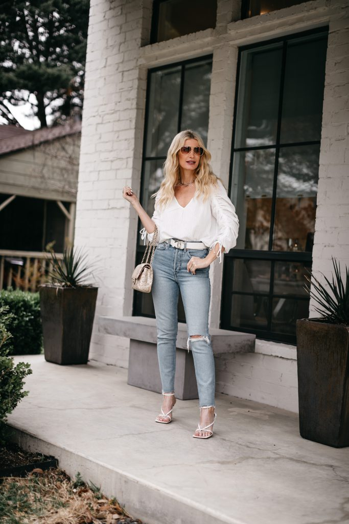 Dallas style blogger wearing a white top and denim with white strappy sandals for summer