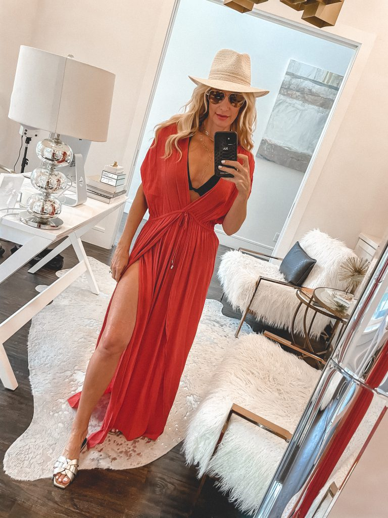 So Heather blog wearing an orange maxi cover up and a black swimsuit for summer with a neutral hat
