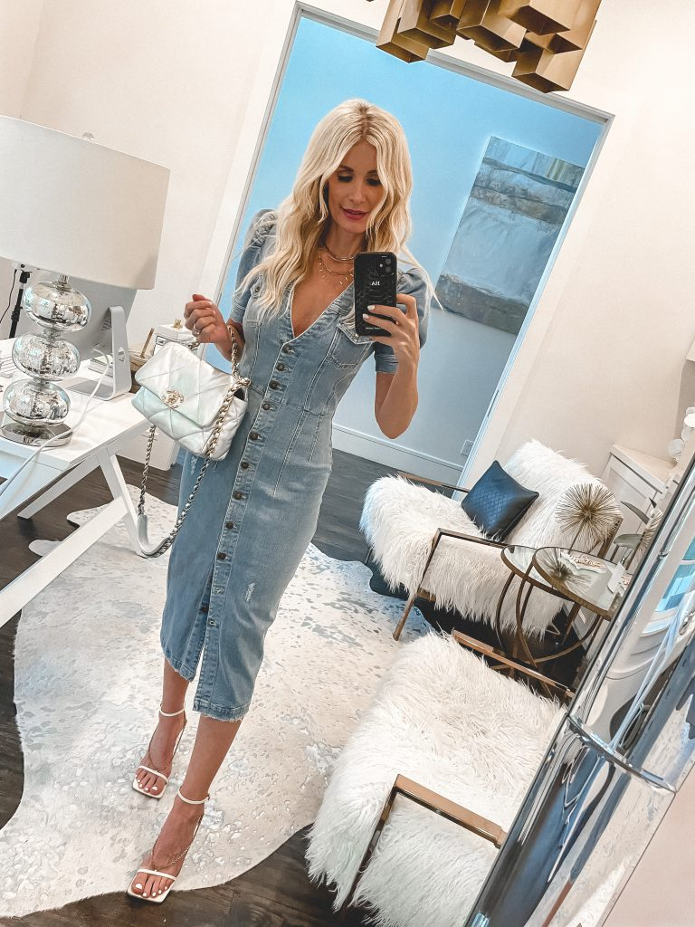 Style blogger wearing a denim midi dress and white heels for summer