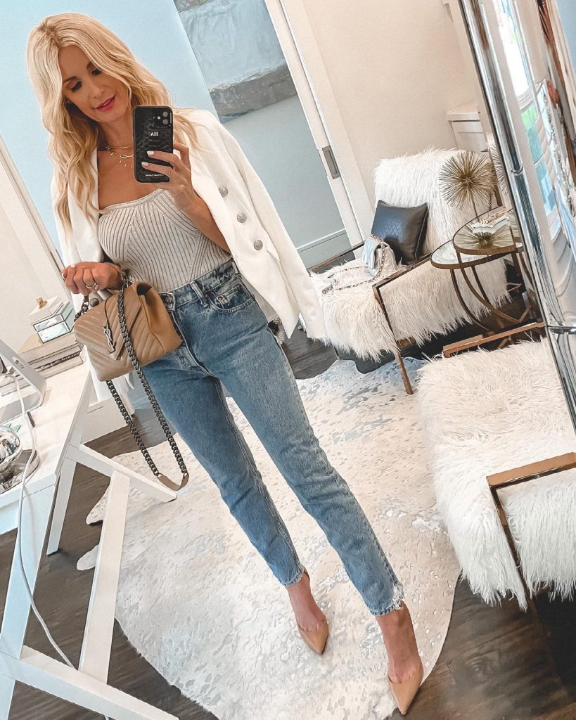 Style blogger wearing a white blazer and high waist jeans