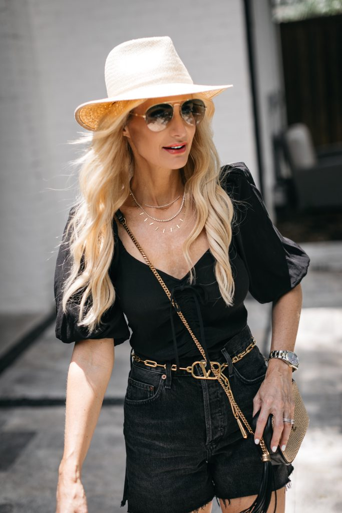 Dallas blogger wearing a black top with puff sleeves and a gold Valentino belt