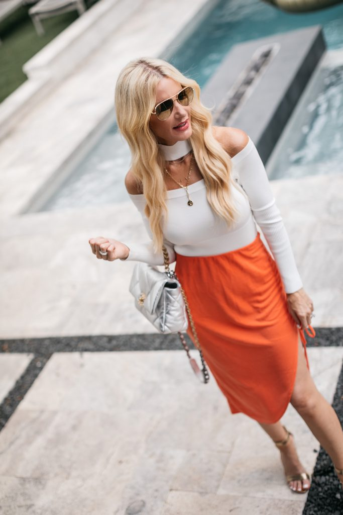 Dallas fashion blogger wearing a cut out white top and an orange midi skirt