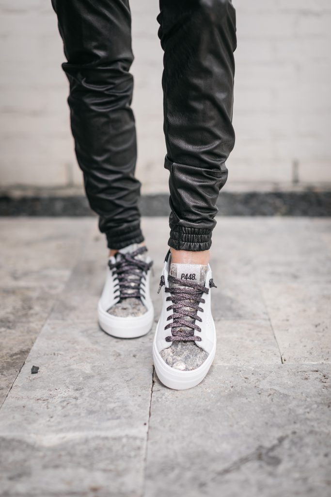 Dallas blogger wearing p448 sneakers and faux leather joggers from the NSALE