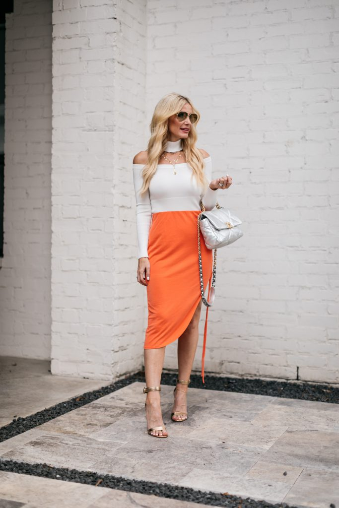 Dallas fashion and style blogger wearing a chic white top and orange midi skirt
