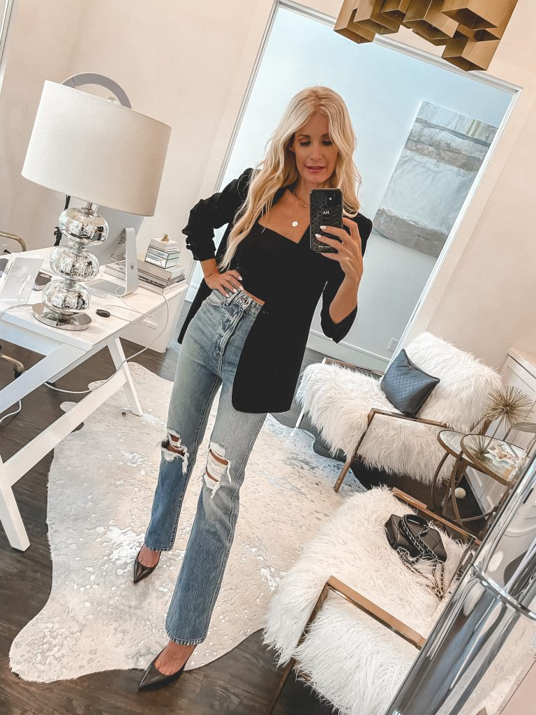 Dallas blogger wearing a black crop top and a black blazer with ripped denim