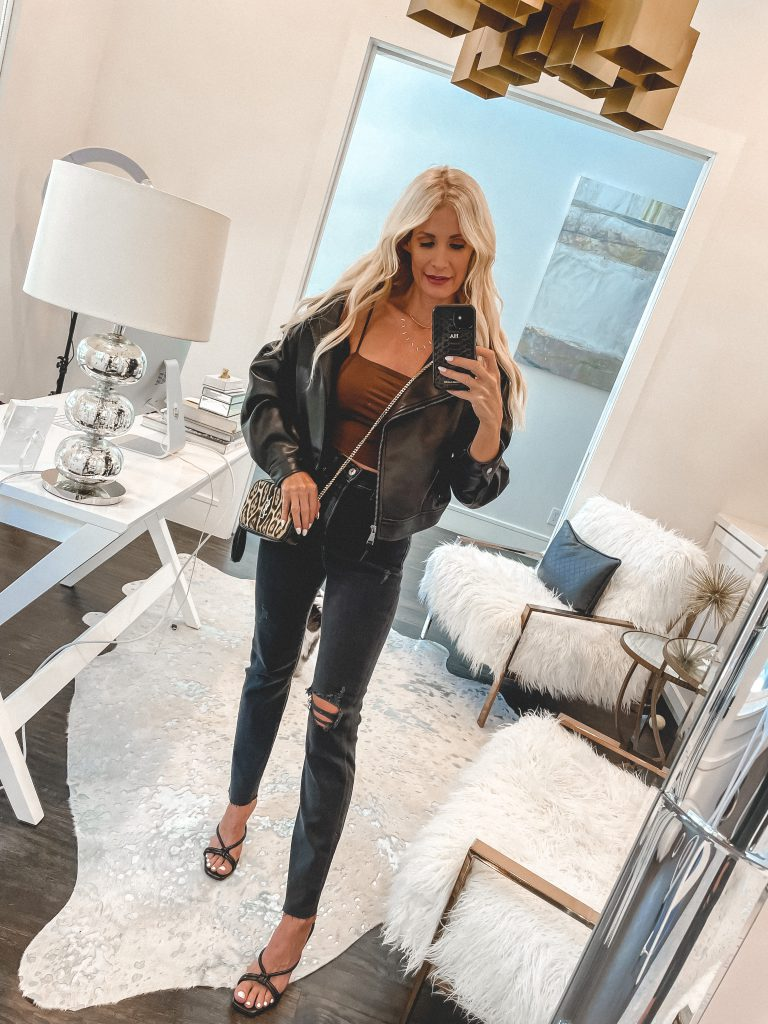 Dallas style blogger wearing distressed black denim and a black moto jacket