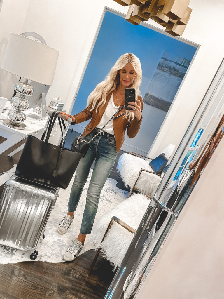 so Heather Blog wearing a camel leather jacket and denim for travel